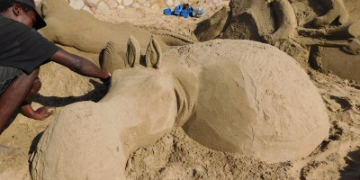 The artist sculpting a sand art hippopotamus on St Michaels on Sea Beach in KwaZulu-Natal