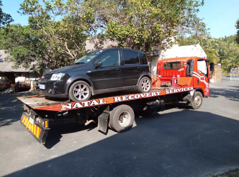 Small black car on a tow-in truck