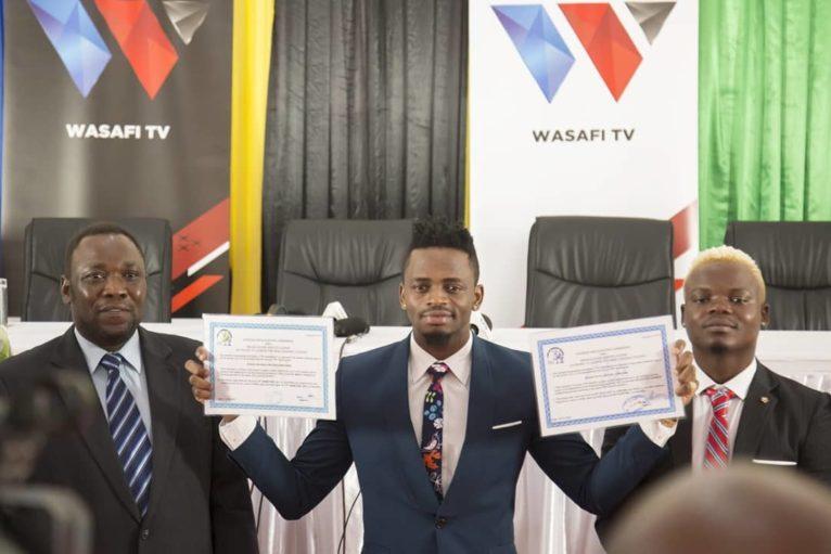 Diamond Platnumz (centre) avec Harmonize (droite) affichant les licenses pour Wasafi FM et Wasafi TV