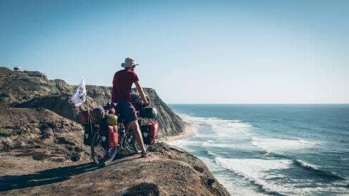 Guillaume de l'équipe Hey Bro au bord d'une falaise au Portugal sur l'Eurovélo 1