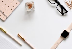 clean desktop with journal, pens, and glasses