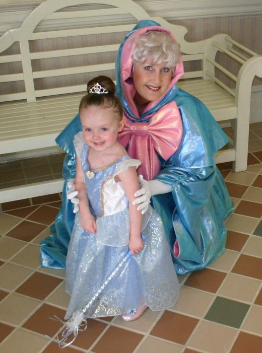 The Fairy Godmother from Cinderella's Dinner with a young guest dressed as Disney Princess Cinderella.