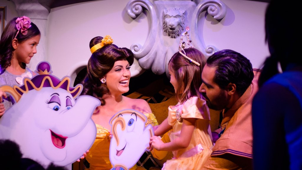 Disney Princess Belle smiles wide at a young girl dressed as Belle with a large crown on her head.