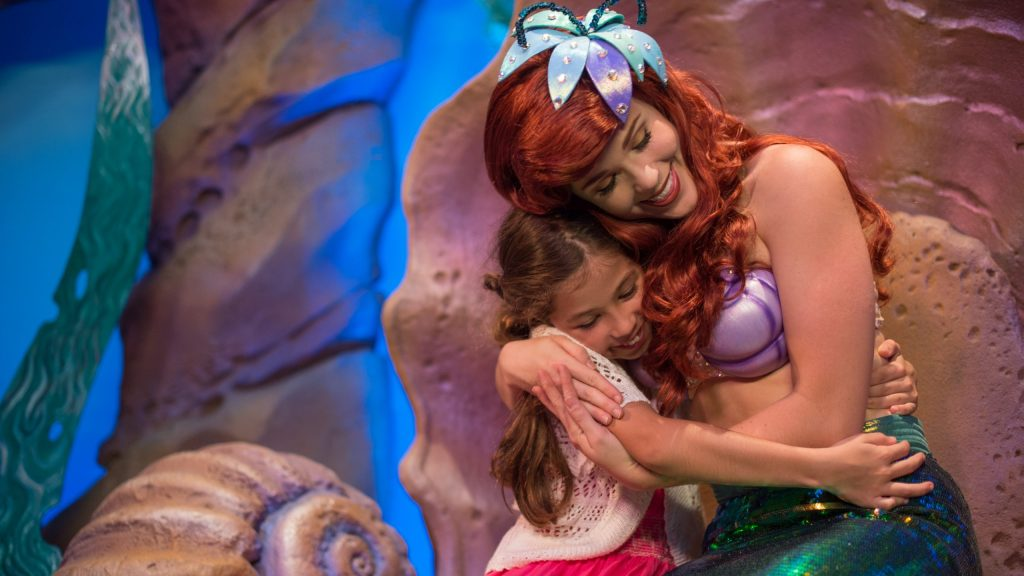 Disney Princess Ariel the Mermaid hugs a little girl at Walt Disney World.