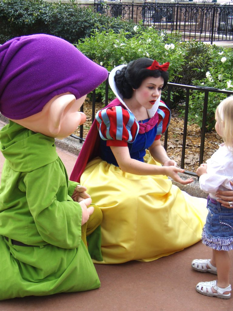 Little girl meeting Snow White Disney character and Dopey the Dwarf.