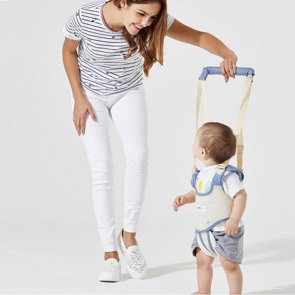 Maman apprend son bébé à marcher avec un harnais