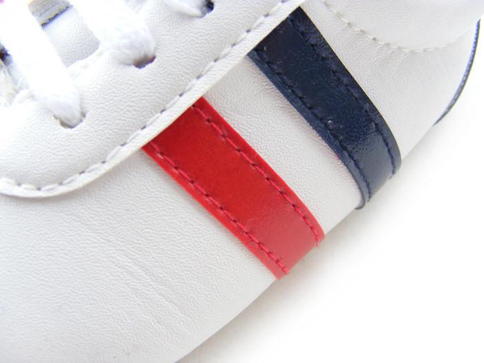 Détail des bandes en bleu et rouge des Baskets blanches