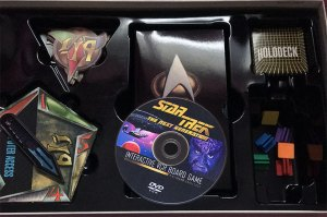 Picture shows the various components of the Star Trek: A Klingon Challenge board game. Items in clude a VHS cassette, A DVD, game cards, spinner and character stands.