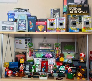 Picture shows two shelves with various retro video gaming knick-knacks displayed on them.