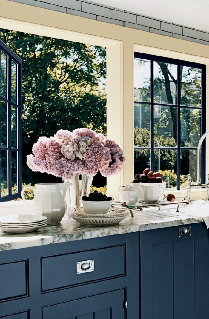 Kitchen with dark blue cabinets, marble top and pink flowers