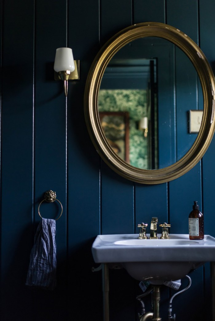 Dark blue powder room with gold mirror