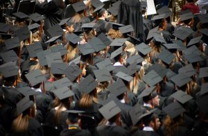 Graduates attend a graduation ceremony wearing black caps