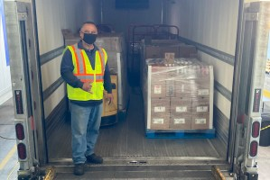 Driver posing with cargo in cargo truck