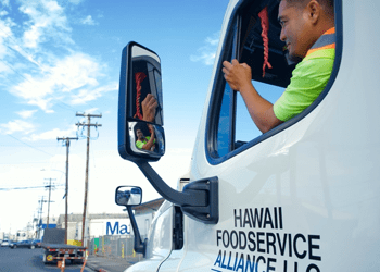 driver looking in rearview window inside company truck