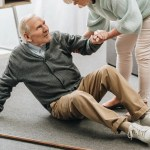 Daughter helping elderly father get off floor after having a fall