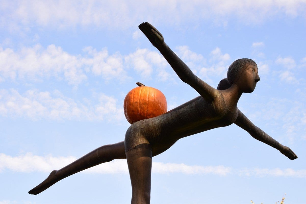 a sculpture of a woman with orange on her back