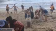 Toeristen maken strand op Koh Samui schoon