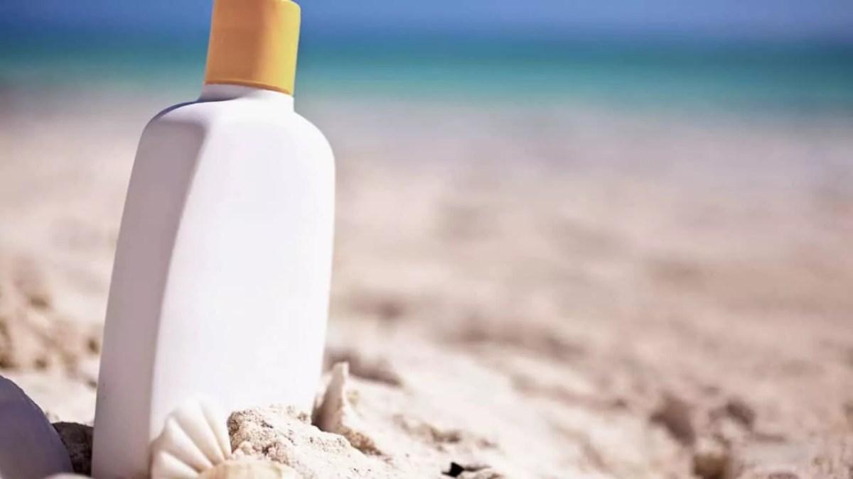 weisse-cremeflasche-in-sandstrand-sonnenschutz