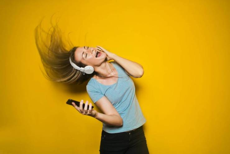 A girl dancing while listening to music via her headphone
