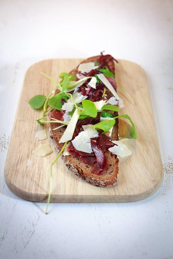Geröstetes Bauernbrot mit Hirschschinken, Parmesan, Postelein und roten Zwiebeln