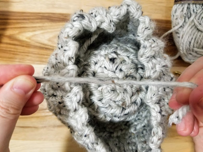 Learn how to make a pom pom using your fingers with this easy to follow photo tutorial. The pom pom is the perfect size for hats, scarves and other crafts. You can make a small, medium or large pom pom simply by using different fingers. #diy #crafts #pompoms #howto