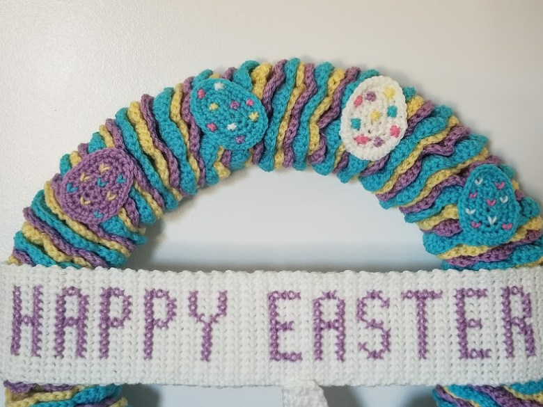 Easter wreath close up of upper part of wreath. 4 eggs and banner