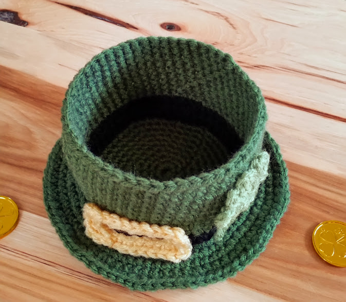 leprechaun hat with buckle and shamrock appliques. photo shows empty hat like a bowl.