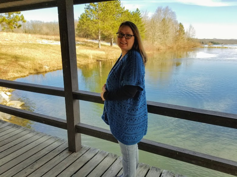 Water's edge kimono in Caron yarn in the color ocean. kimono on woman standing on a bridge in front of a lake