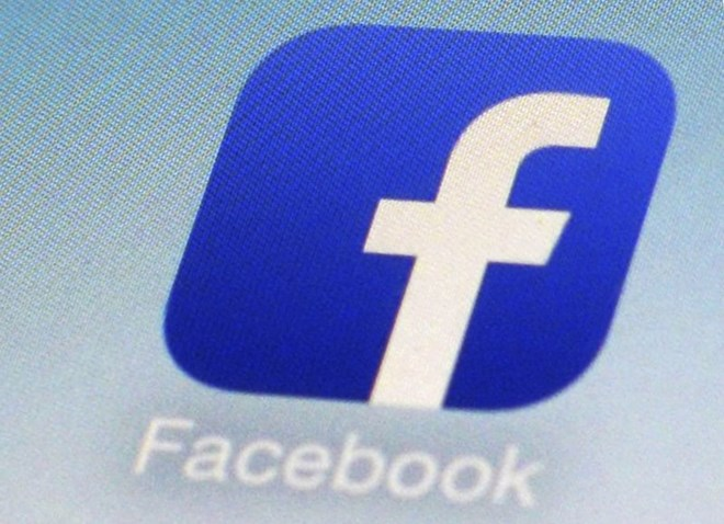 This Feb. 19, 2014, file photo, shows a Facebook app icon on a smartphone in New York. The Australian government said on Friday, July 31, 2020 it plans to give Google and Facebook three months to negotiate with Australian media businesses fair pay for news content. (AP Photo/Patrick Sison, File)