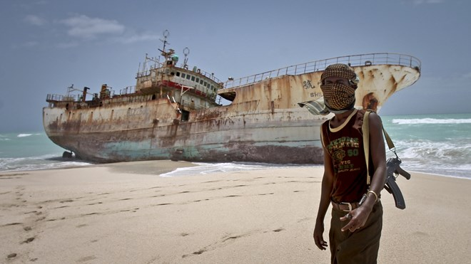 A masked Somali pirate stands near a Taiwanese fishing vessel that washed up in 2012 after the pirates were paid a ransom and released the crew. The image appears on the cover of Michael Scott Moore's new book The Desert and the Sea. Farah Abdi Warsameh/AP