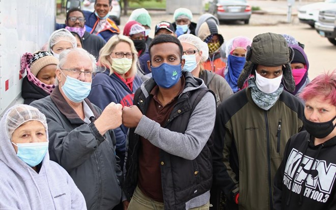 Employees of Salad Makers Inc., who dress warmly to work in a chilled facility, gather around owner Tom Jacobson and Moorhead Human Rights Commissioner Cani Adan as they bump fists Wednesday, Sept. 16, after successful labor negotiations. C.S. Hagen / The Forum
