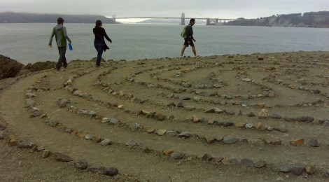 Several people walk the meditation labyrinth at Lands End Point with Golden Gate Bridge in the background.