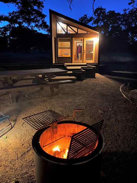 cabin at night with lights on and fire pit
