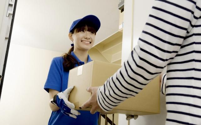引っ越し荷物を手渡す宅配業者の女性