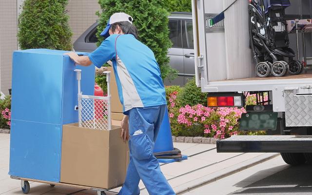 引越業者がトラックの荷物を運ぶ様子