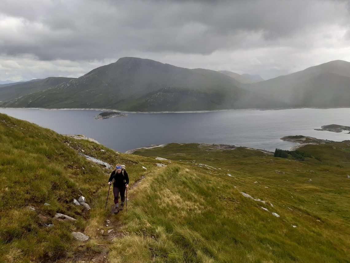 Walking up a hill with Loch Quoich on the background.