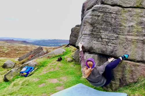 A woman outdoor bouldering at Stanage Edge in the Peak District