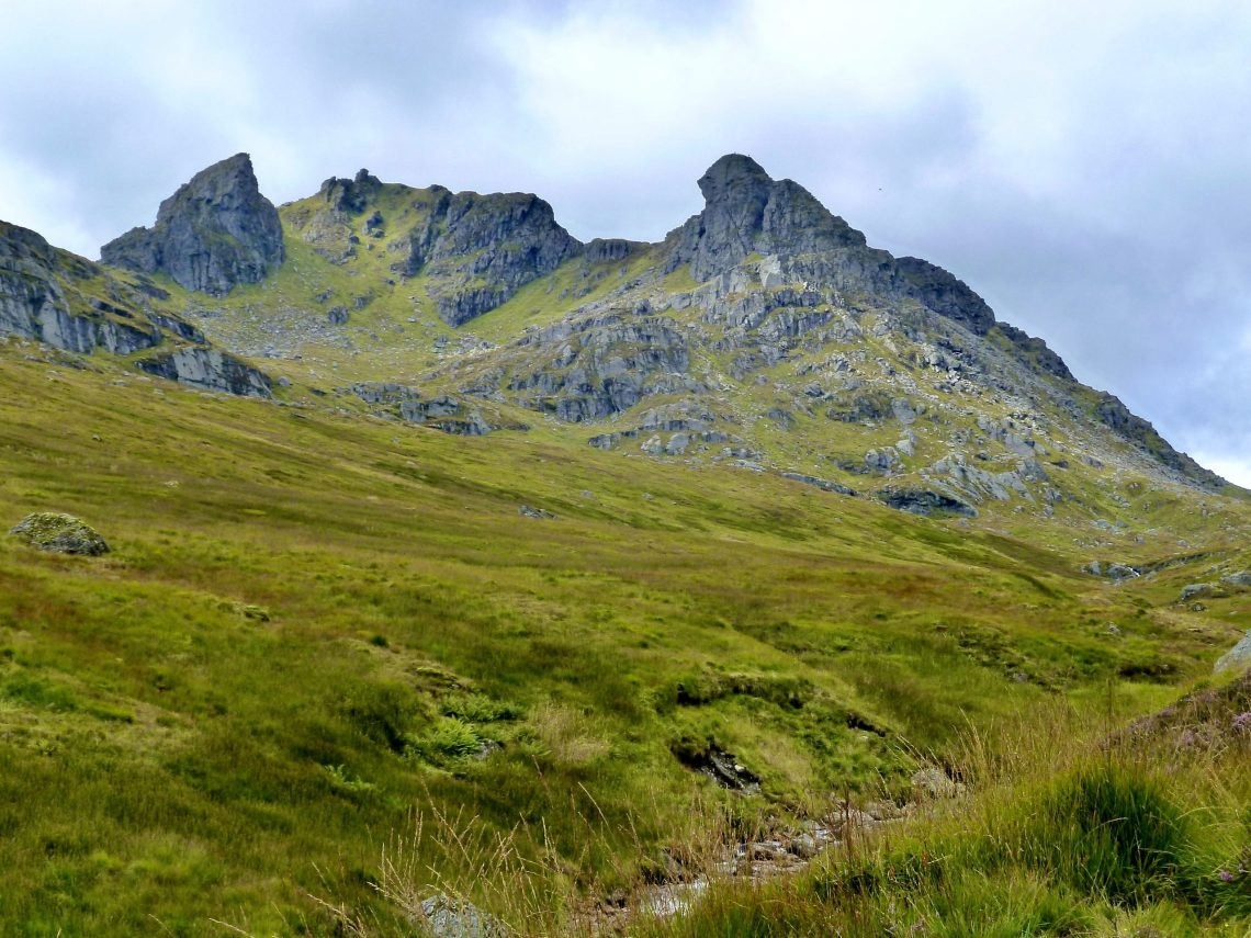 A rocky mountain in the Scottish Highlands with a lush green foreground and a grey sky.