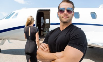 Confident bodyguard wearing sunglasses while standing against woman and private jet