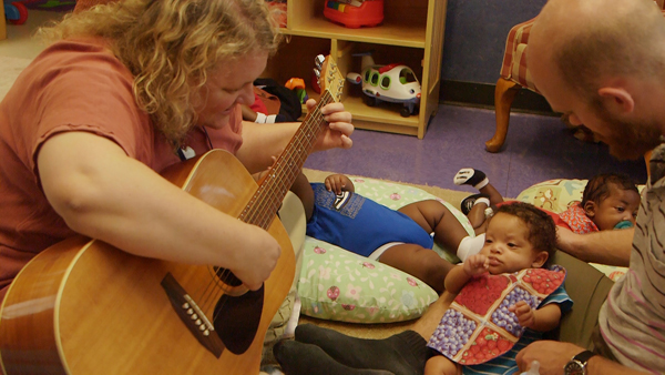 Deanna Hanson-Abromeit, assistant professor of music education and music therapy at the University of Kansas, is studying how music helps premature infants survive and thrive. Here, she strums the guitar for children at Operation Breakthrough, an early education child care and social services facility in Kansas City, Mo. KHI News Service
