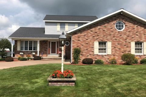 picture of house with landscaping at front porch and front of garage by Hillside Seasonal Services