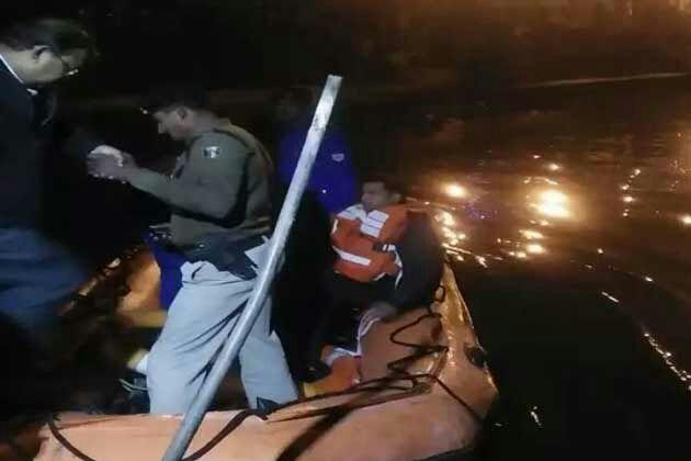 फोटो~रात के अंधेरे में हादसे के शिकार लोगों को नदी में तलाशती एनडीआरएफ की टीम।