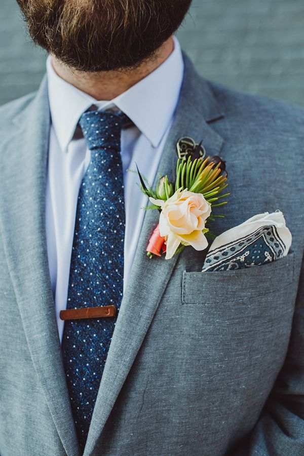 light gray fall and winter groom wedding suit and peach boutonniere