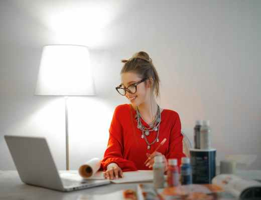 woman in red long sleeve shirt looking at her laptop