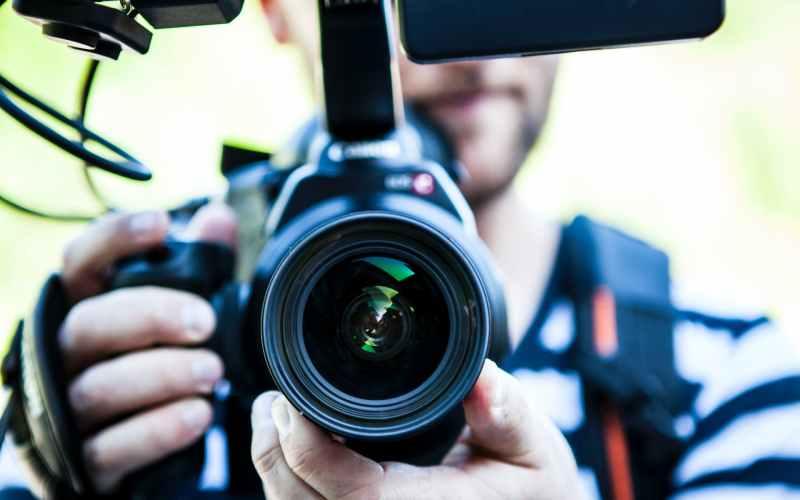 person holding canon dslr camera close up photo