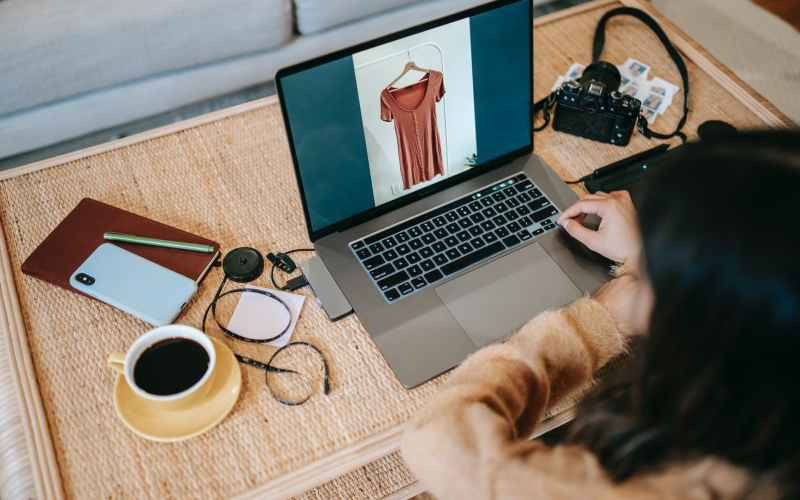 crop photographer using laptop with photo on screen near coffee