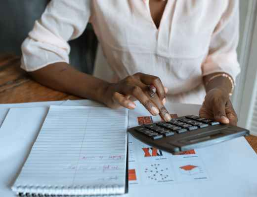 person in white dress shirt using a calculator
