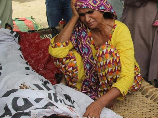 Mother of social media celebrity Qandeel Baloch mourns alongside her body during her funeral in Shah Sadar Din village, around 130km from Multan in Pakistan. (AFP photo)