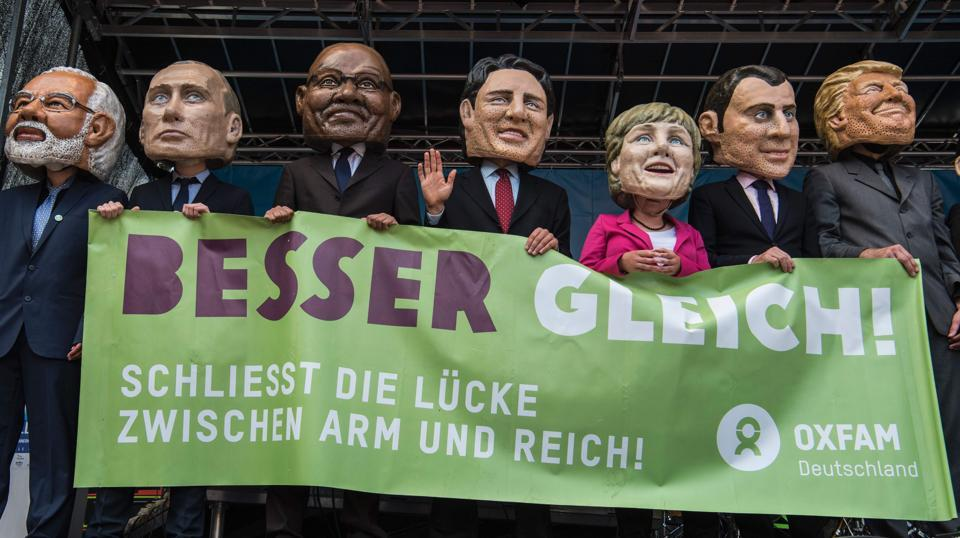 Performers wearing masks of world leaders hold a placard reading 'Better off equal! Close the gap between rich and poor' during a demonstration ahead of the G20 summit in Hamburg. (John Macdougall / AFP)