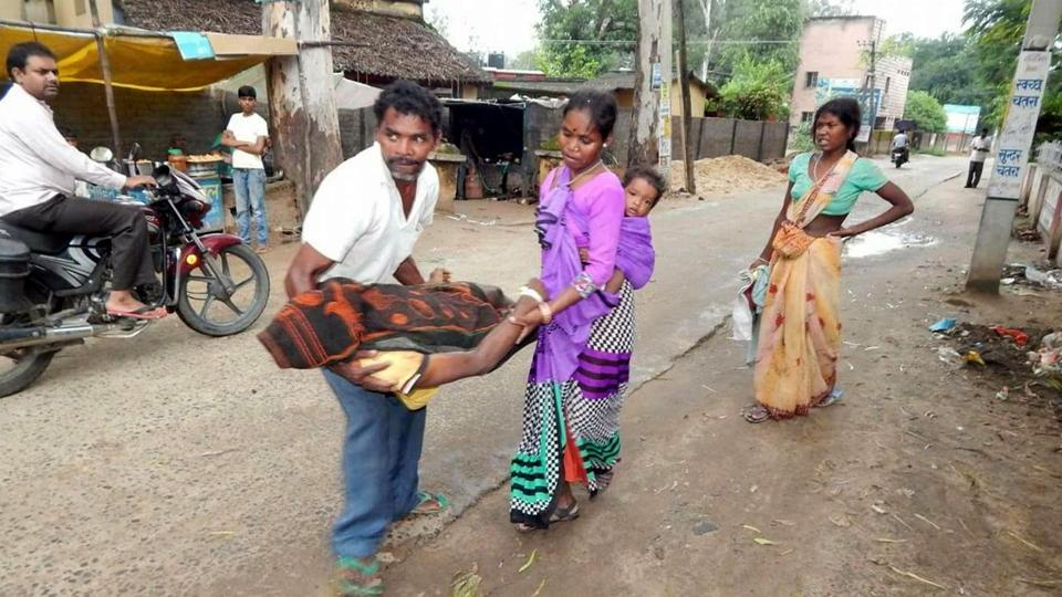 Shidpa village residents, Lakshman Oraon and his wife Sita Devi carry the body of his younger brother Rajendra Oraon from Sadar hospital in Chatra district of Jharkhand as Rajendra's wife Sunita Devi follows, wailing. Rajendra's infant son is tied to Sita's back.
